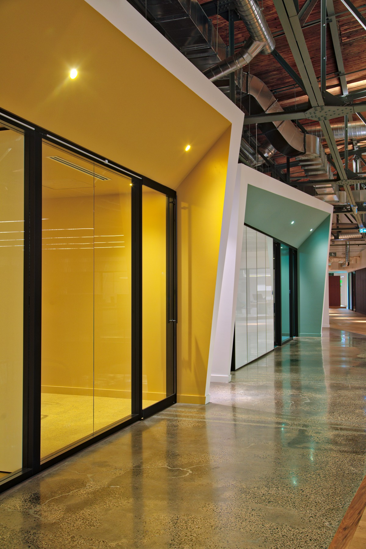 The multi-coloured, and geometric volumes of closed offices and conference rooms on the second floor are colour matched to the ceiling using the RAL color rendering capabilities of the Discreet Nano luminaires.
