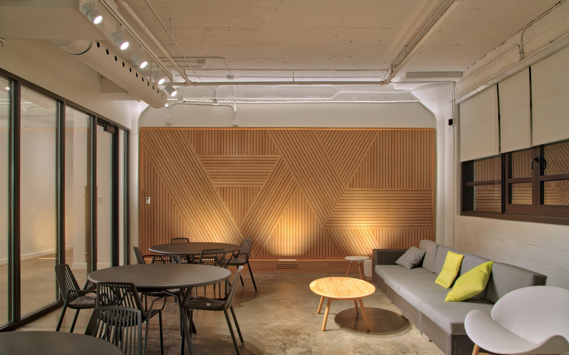 The wood paneling in the open office area is uplit using Lumenfacade projectors.